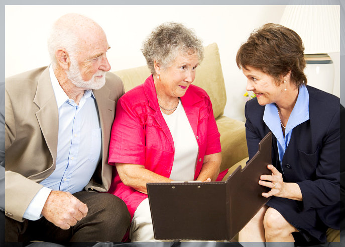 Senior couple listens to a sales pitch in their home